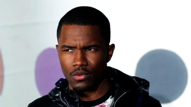 Ein dunkelhäutiger, junger Mann mit kurzem Haar und einer Kaputzenjacke, er schaut ernst.