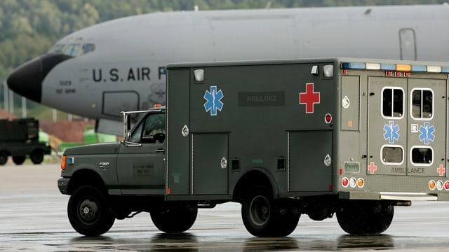 Ein Krankenwagen, im Hintergrund eine US-Transportmaschine.