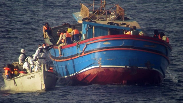 Ein Schiff der italienischen Küstenwache nimmt Flüchtlinge von einem Boot an Bord