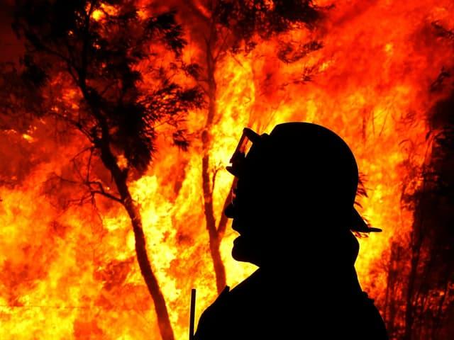 Feuerwehrmann als schwarze Silhouette vor brennendem Wald in Australien.