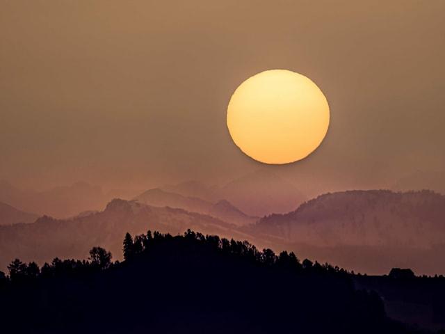Bräunlicher Himmel mit gelber Sonnenscheibe. Im Vordergrund dunkle Konturen von Hügeln.