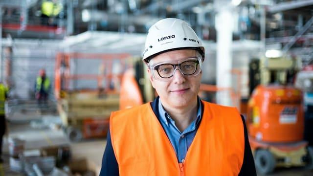 Ein Mann mit Helm und Leuchtweste steht in einer Fabrikhalle.