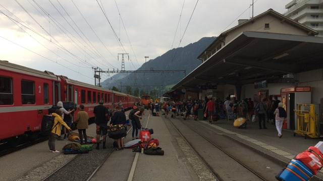 Persunas che arrivan a Glion cun tren cun tendas e gronda bagascha.