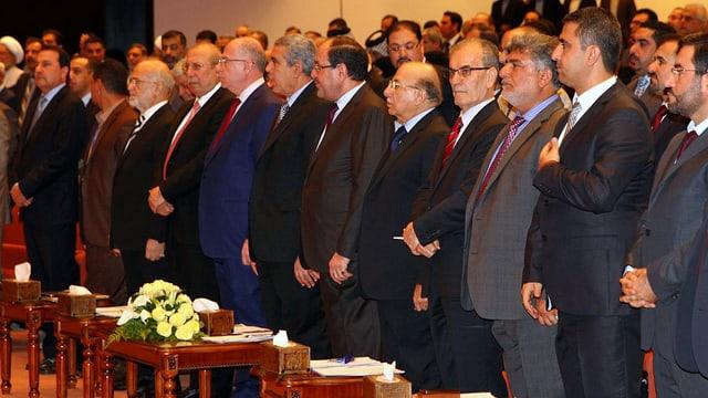 Männer in Anzügen,In einem Saal stehend.
