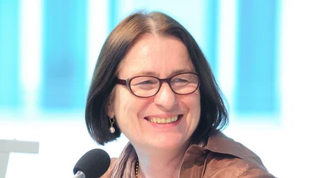 Das Porträt einer Frau mit mittellangen, dunkelbraunen Haaren und Brille.