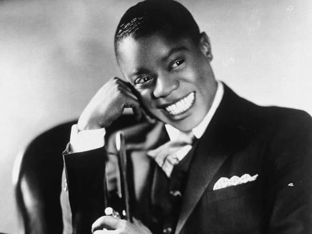 Louis Armstrong in jungen Jahren, der seinen Kopf auf seine Hand stützt