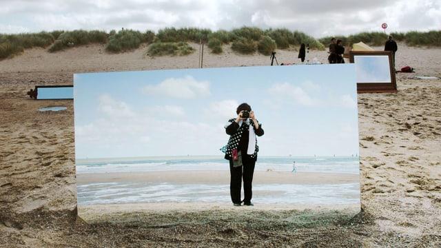 An einem Sandstrand steht ein grosser Spiegel, darin ist Varda mit Fotoapparat zu sehen.
