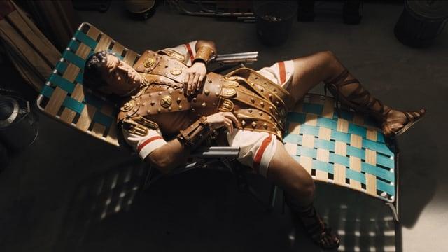 George Clooney in einer Art Ben-Hur-Rüstung, auf einem Liegestuhl liegend