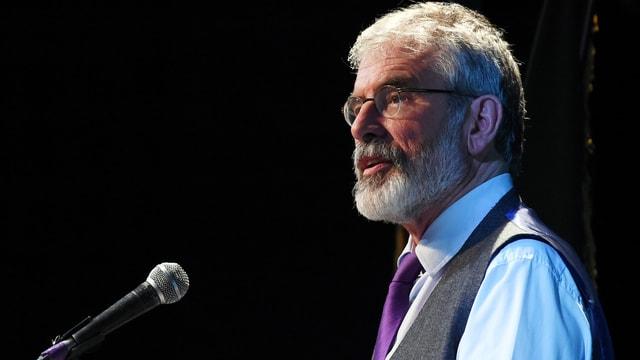 Adams spricht vor schwarzem Hintergrund in ein Mikrofon, Profil-Aufnahme.