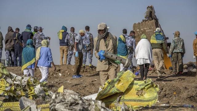 Man sieht Überreste eines Flugzeuges und Menschen, die den Absturzort untersuchen.