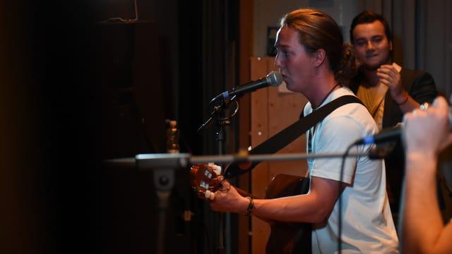 Ina giuven cun ghitarra al microfon sin in palc.