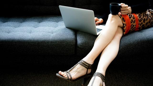 Eine Frau sitzt schick gekleidet vor dem Computer.