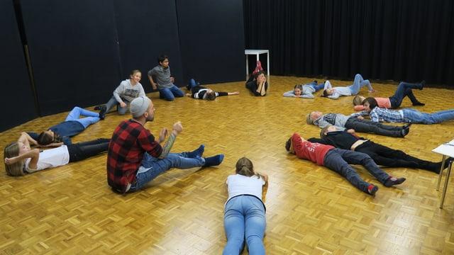 Kinder liegen in einem grossen Raum im Kreis formiert auf dem Boden.