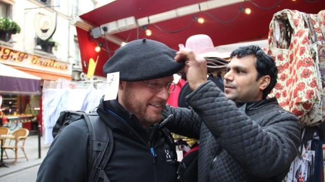 Il reporter da RTR avant in stand da via nua ch'i vegn vendì tastgas e chapès. In marchadant metta si a Stefan Dobler in beret.