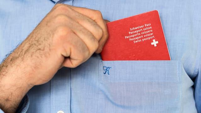 Mann steckt Schweizer Pass in Hemdtasche.