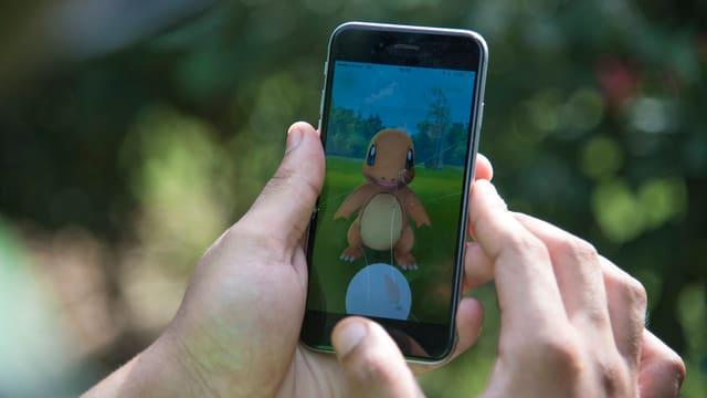 Handy, auf dem Bildschirm eine Animationsfigur, zwei Hände halten das Handy.