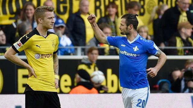Der Dortmunder Marco Reus blickt verständnislos, der Darmstädter Marcel Heller ballt die Faust.