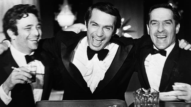 Drei Männer im Anzug und mit Fliege sitzen lachend an einer Cocktailbar.