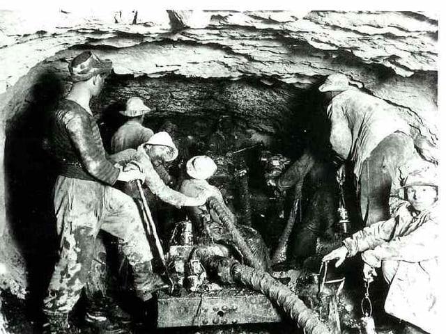 schwarz-weiss-Foto von Arbeitern in einem engen Stollen