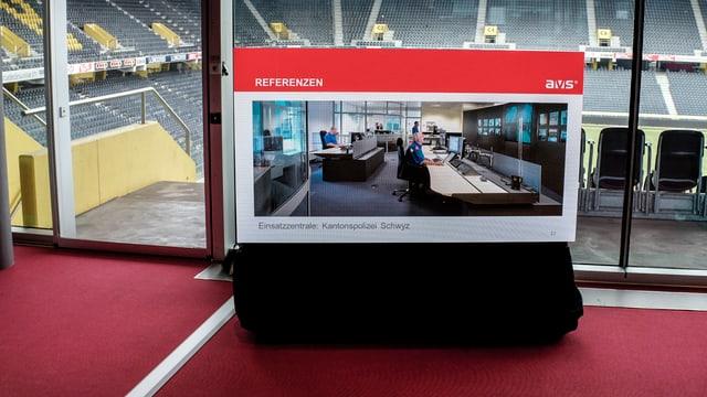 Foto einer Einsatzzentrale auf einem Flachbildschirm, im Hintergrund das Stadion