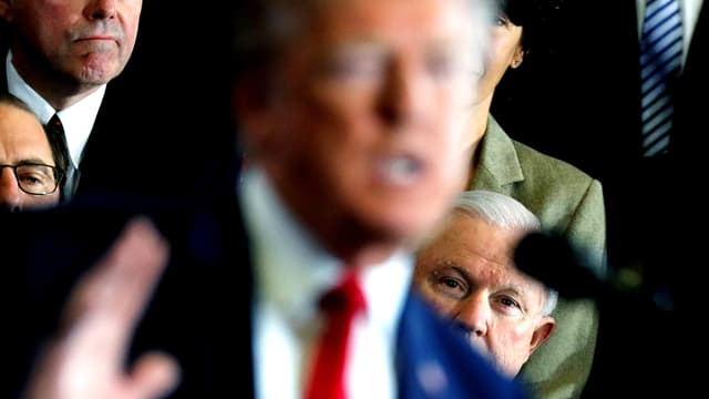 Im Vordergrund Donald Trump in der Unschärfe. Hinter ihm schaut Vizepräsident Jeff Sessions hervor.