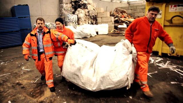 Drei Männer in orangen Uniformen tragen einen riesigen Müllsack.