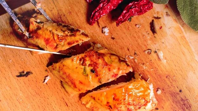 Poulet-Brust wird in drei Stücke geschnitten.