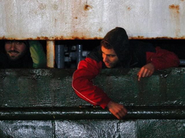 Zwei Flüchtlinge schauen aus einer Schiffsluker heraus.