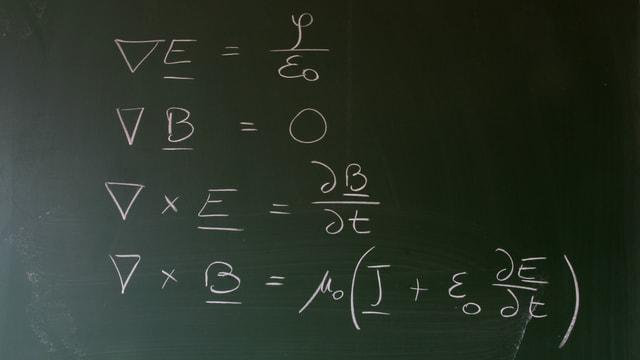 Maxwells Gleichungen in weisser Kreideschrift auf einer Schultafel.