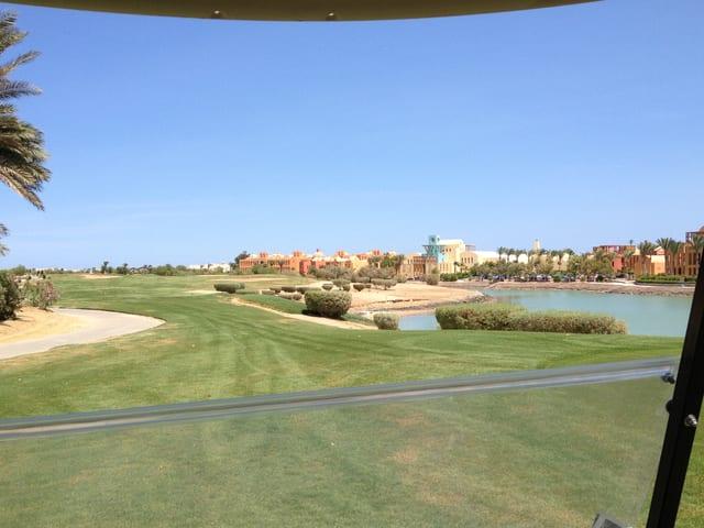 Leerer Golfplatz mit Hotel im Hintergrund.