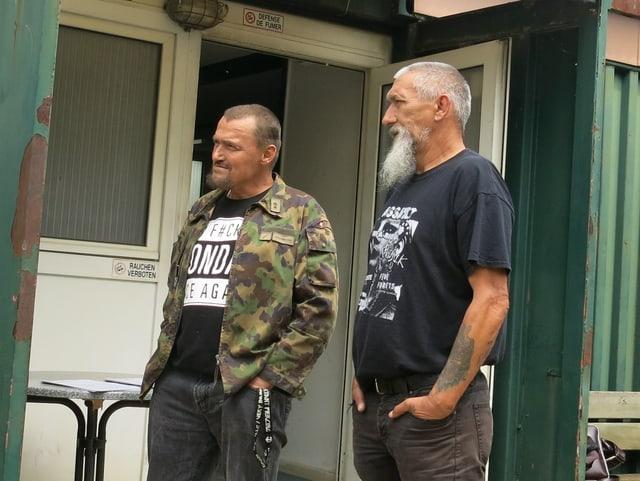 Zwei Männer mit den Händen in den Taschen.