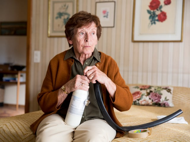 Frau sitzt auf Bett und schliesst einen Schlauch an eine Art Gasflasche an