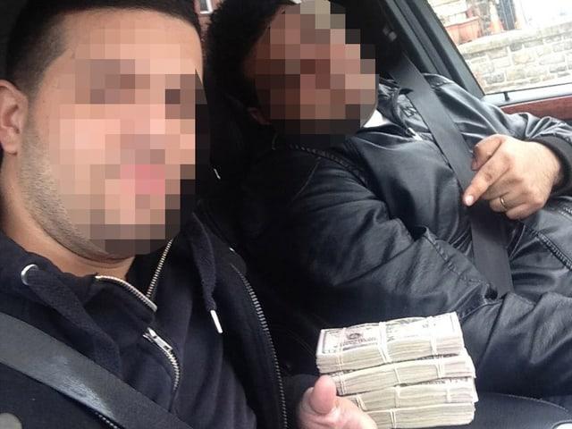 Zwei Männer präsentieren stolz ein Bündel von Dollarnoten