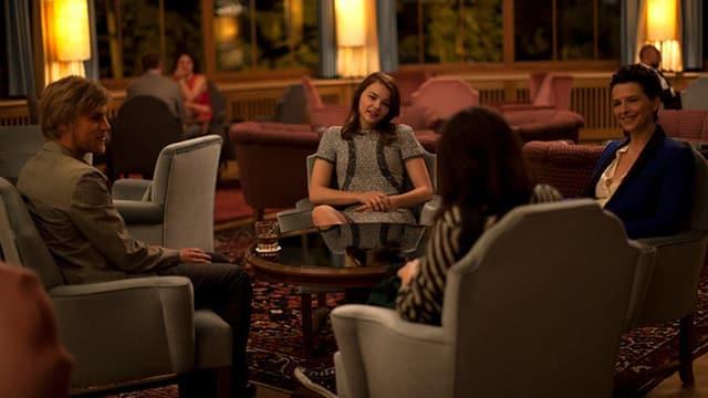 Vier Menschen sitzen um einen Tisch in einer Hotellobby