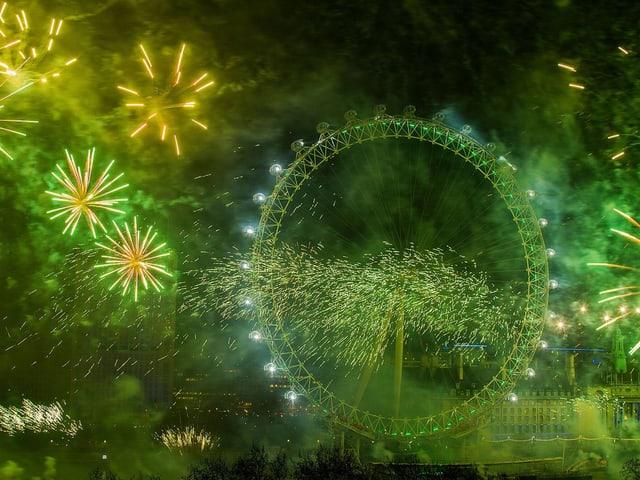 Das Riesenrad im grünen Licht von explodierendem Feuerwerk.