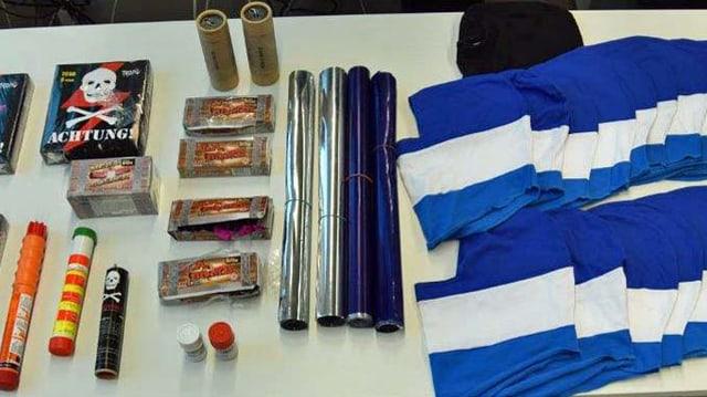 Konfiszierte Knallkörper, Pyrofackeln und Sturmhauben liegen auf einem Tisch.