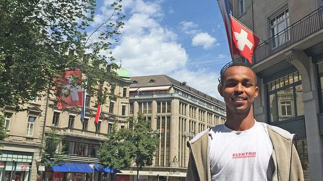 Ein Mann steht vor einem Gebäude, an dem eine Schweizerfahne weht.