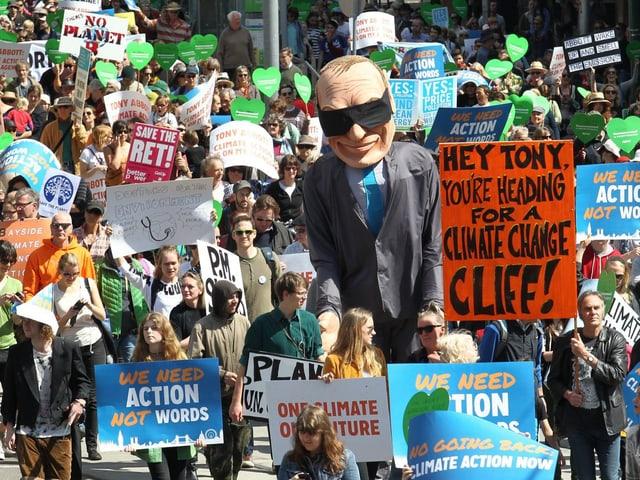 Hunderte von Demonstranten mit Transparanten. Darunter auch eine übergrosse Puppe, die Tony Abbott darstellt.