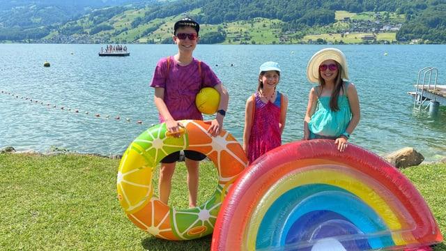 Moritz, Ella und Paula stehen vor dem Sarnersee. Es ist sonnig.