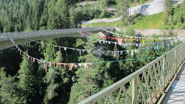 Bunte Kleidungsstücke sind auf eine Wäscheleine zwischen zwei Brücken gespannt.