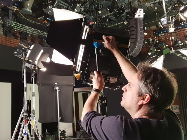 Der Chef-Kameramann Matthias Bolliger hantiert an einem grossen Studio-Scheinwerfer herum.