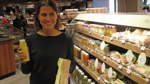 Lisa Savenberg von der Migros mit einem frischgepressten Saft und einem Sandwich in der Hand.