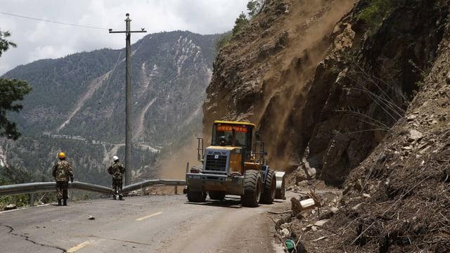 Zwei Arbeiter und ein Bagger versuchen, eine verschüttete und beschädigte Strasse vom Geröll zu säubern.