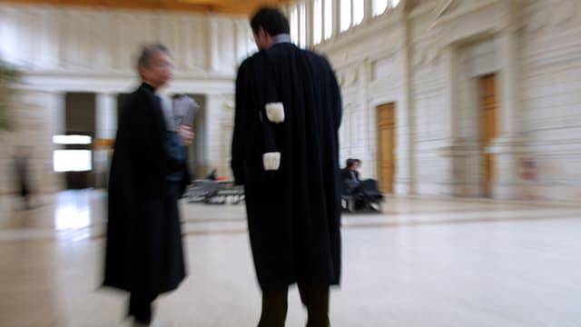 Zwei Männer in schwarzem Mantel stehen in einer Halle.