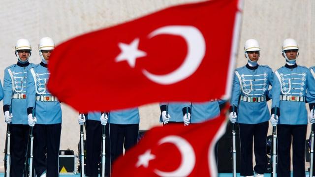 Eine Reihe von Gardisten in hellblauer Uniform steht stramm vor einer türkischen Flagge.