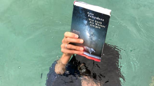 Annette König ist unter Wasser und hält das Buch von Anja Kampmann «Wie hoch die Wasser steigen» über das Wasser