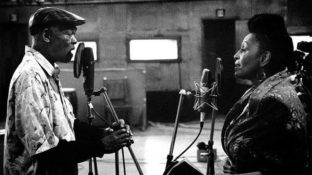 Schwarzweissbild: Ein Mann und eine Frau stehen sich in einem Tonstudio gegenüber und singen in Mikrofone