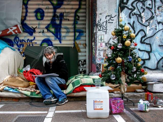 Ein Obdachloser sitzt auf einem Stapel aus Wolldecken, neben ihm ein Tannenbaum.