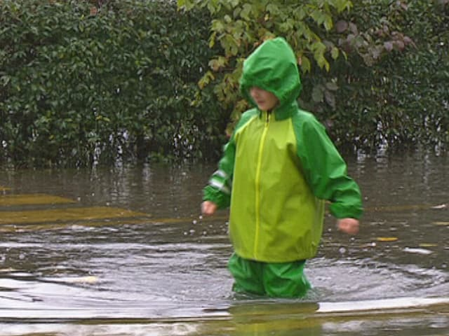 Ein Kind im Regenzeug stapft durch knietiefes Wasser.