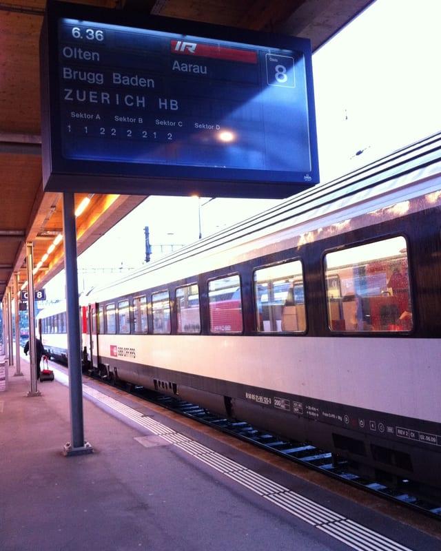 Ein Zug fährt am Bahnhof ein. Auf einer Tafel wird angezeigt, dass der Zug um 6 Uhr 36 Minuten nach Aarau fährt.